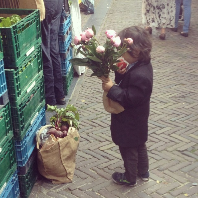 A little child in a suit, chomping on a tomato whilst at the markets in Amsterdam. Moments like these still bring such a big smile to my face.